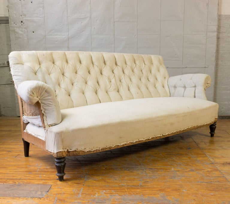 Napoleon III tufted sofa with rolled arms in muslin. Price includes refinishing of legs. This piece is very good condition with no work needed prior to upholstery. 