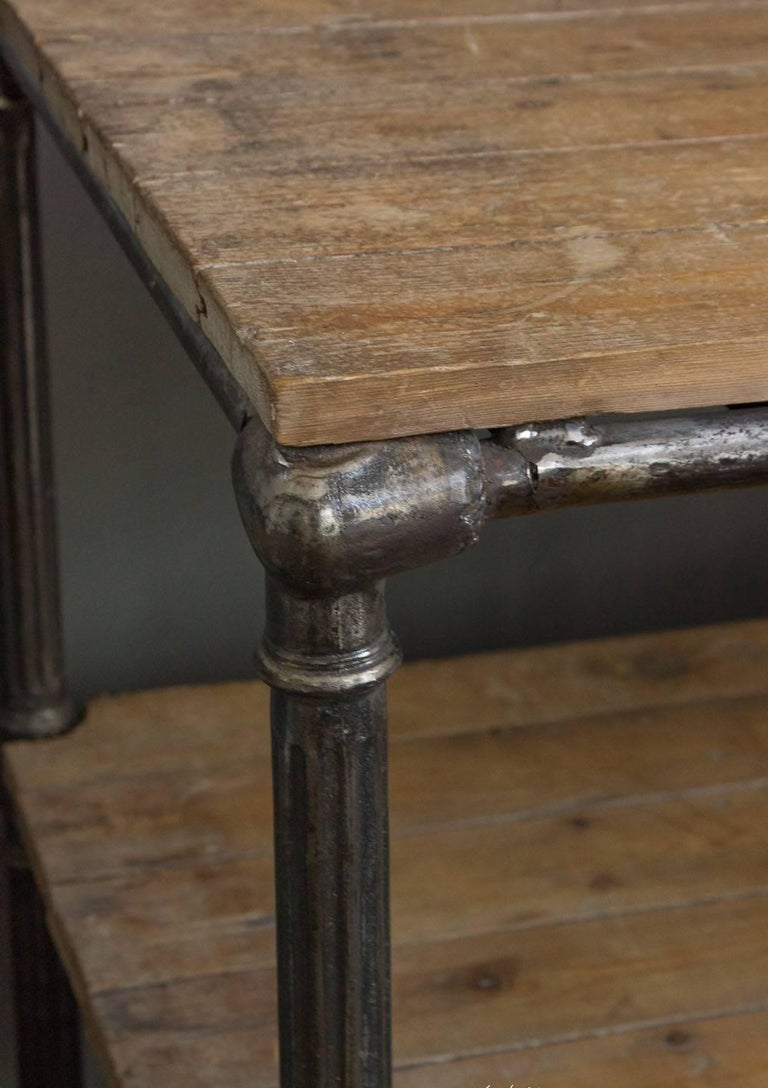 A French early 20th century industrial console with modeled cast iron legs and two shelves.