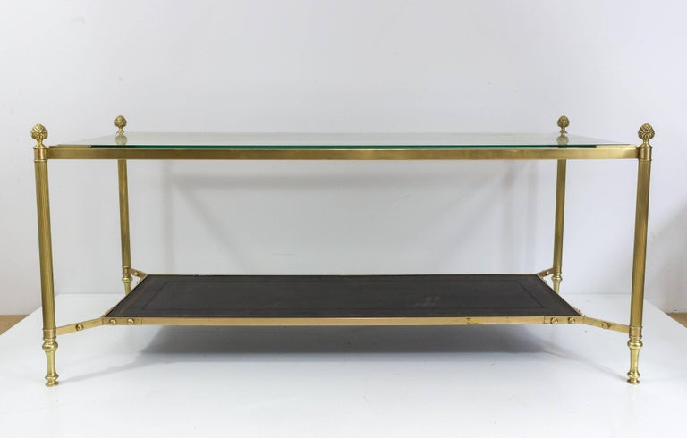Brass coffee table with a clear glass top shelf and a black tooled leather lower shelf completed with pine cone finials. French 1940s, in the style of Maison Jansen.
