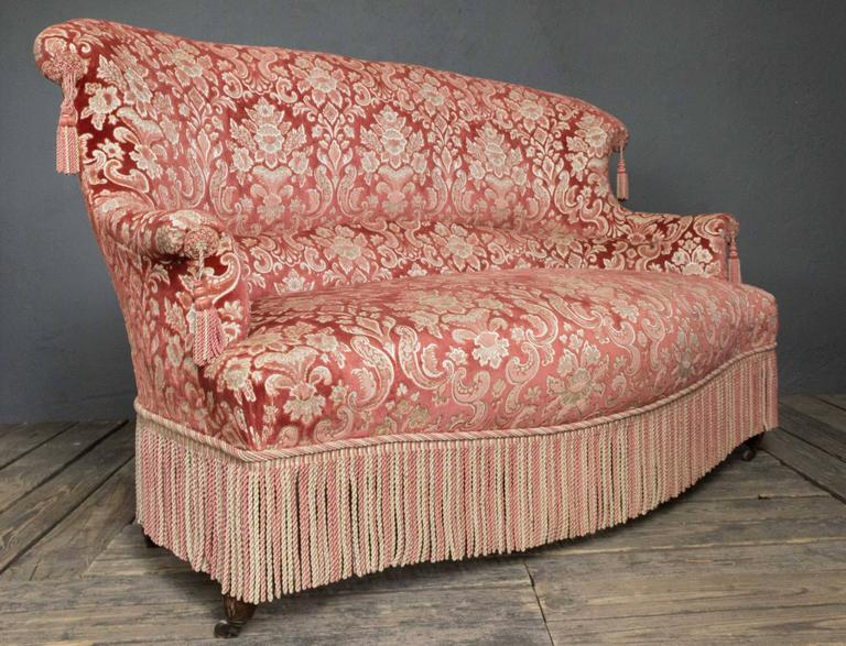 Large Napoleon III settee in crushed red and cream pattern velvet. Bouillon fringe wraps around front and sides of settee with tassels on arms and back.