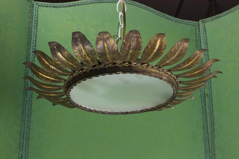Spanish 1940s gilt sunburst ceiling fixture with round frosted glass; framed with two rows of braiding.  This fixture has been UL Certified Code Wired and is sold with a matching canopy.  UPS Shipping quote available on request.