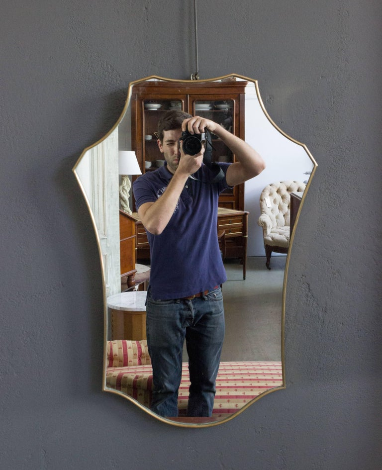 Italian 1960s shield form mirror with brass frame.