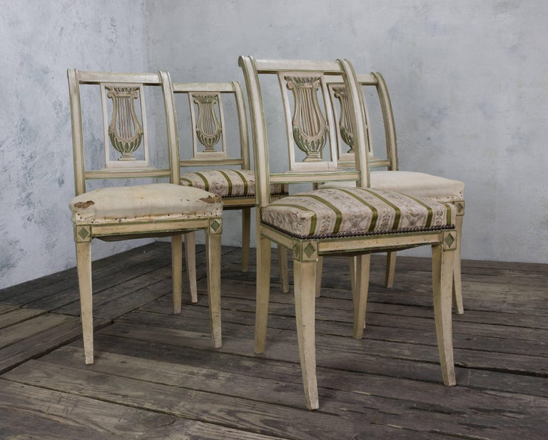 Set of four Directoire style dining room chairs, circa 1920, in original green and off-white patina. Original upholstery on two and muslin on two.