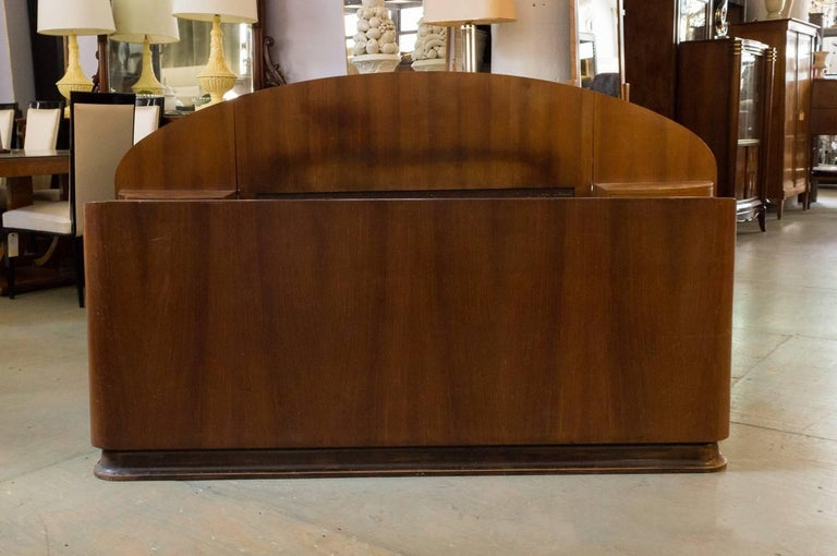 French deco mahogany bed frame with built in nightstands. This piece is need of polishing to bring out its true potential. It fits a double bed. This piece is mahogany veneered. Because of the simplicity of the design it could easily be extended
