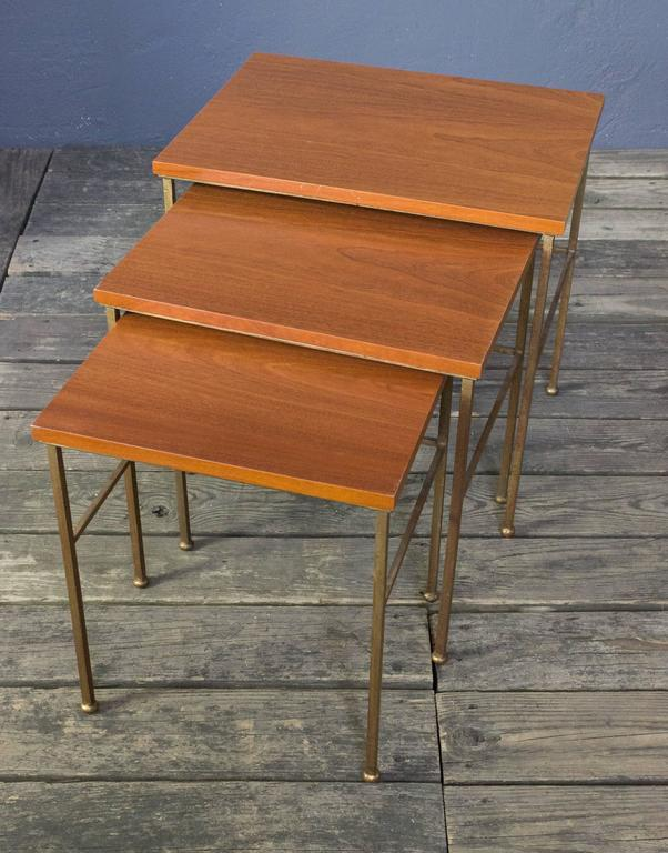 Set of French 1940s nesting tables; hand-forged iron bases with gilt finish and recently restored mahogany veneered tops.