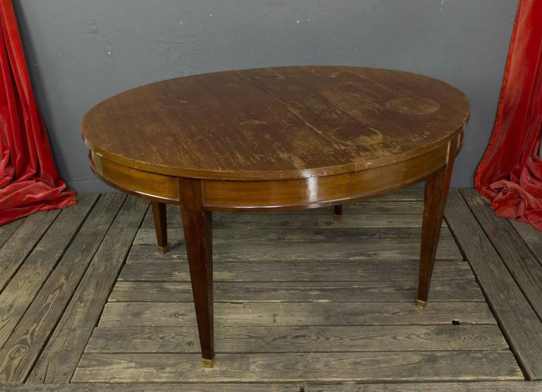 French 1940s mahogany veneered oval dining table with the brass sabot. The table can open to 90