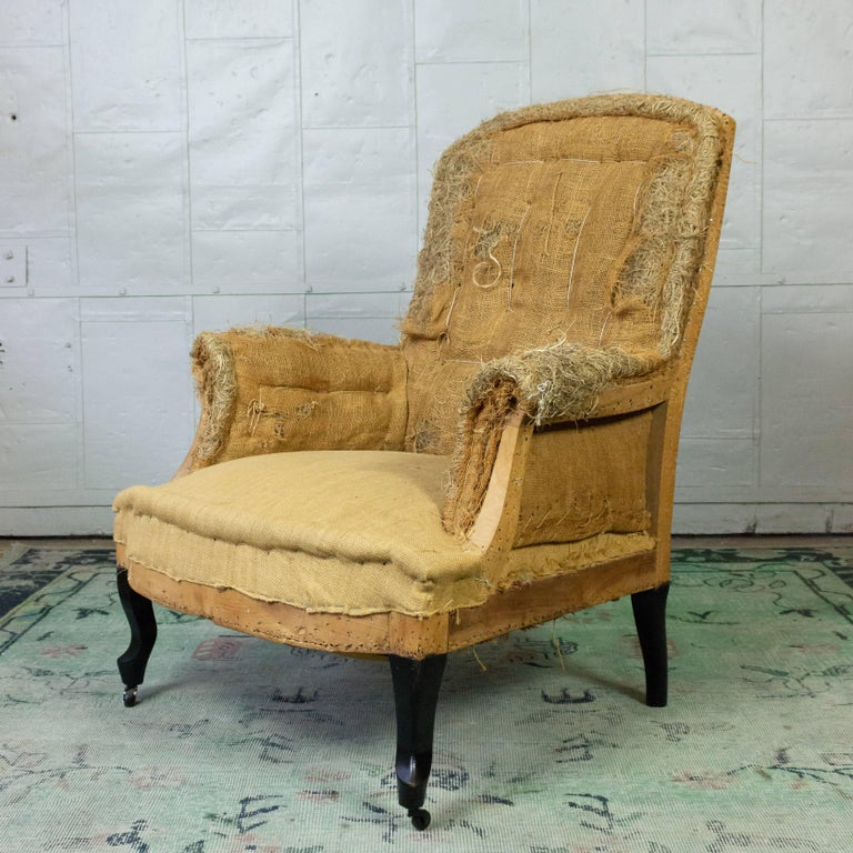 French 19th century armchair in with ebonized cabriole legs stripped down to the muslin and burlap. Ready to be upholstered, Sold as is.