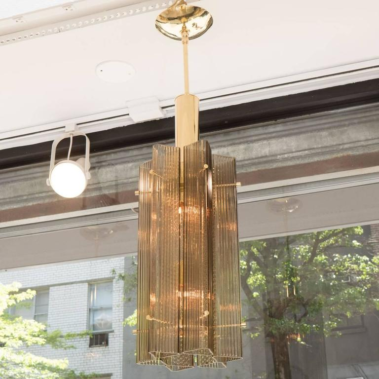 Brass pendant ceiling fixtures composed of clustered smoked and fluted glass tube elements.