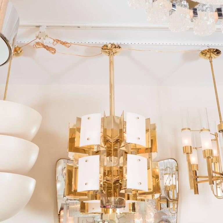 Cylindrical two-tiered brass chandelier featuring rectangular resin shades.