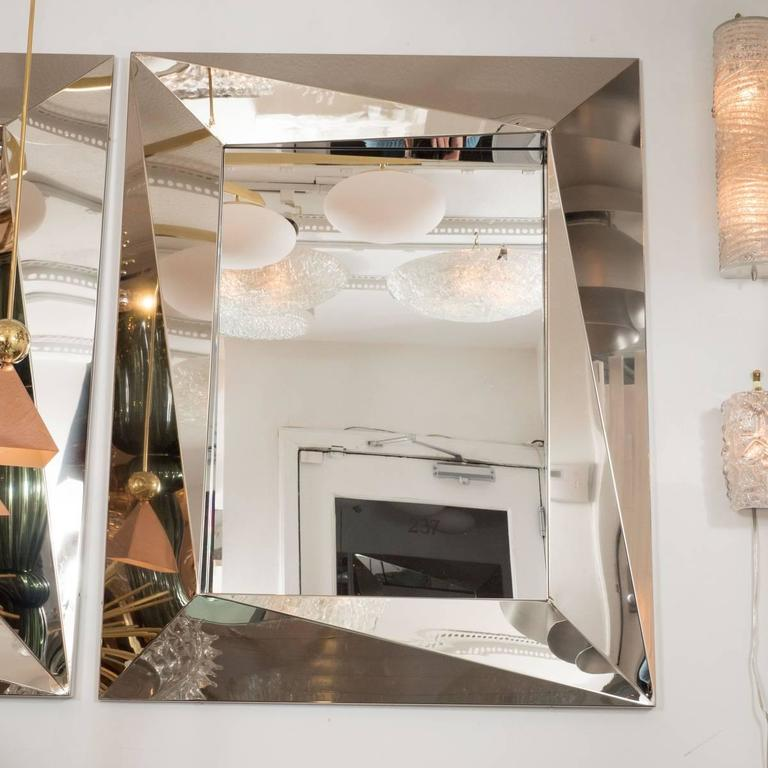 Polished stainless steel mirror with faceted surround.