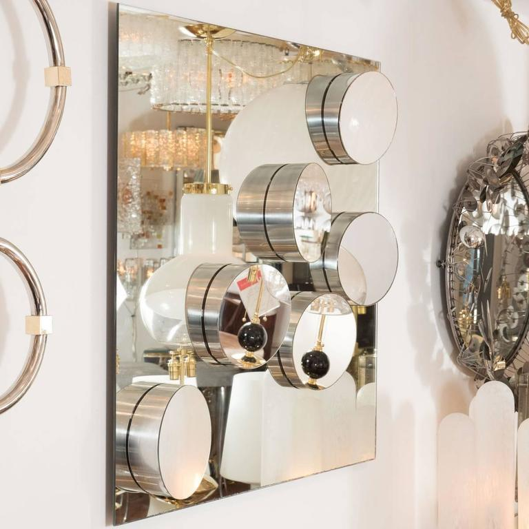 Decorative mirror with applied, sloped details featuring stainless steel frames.