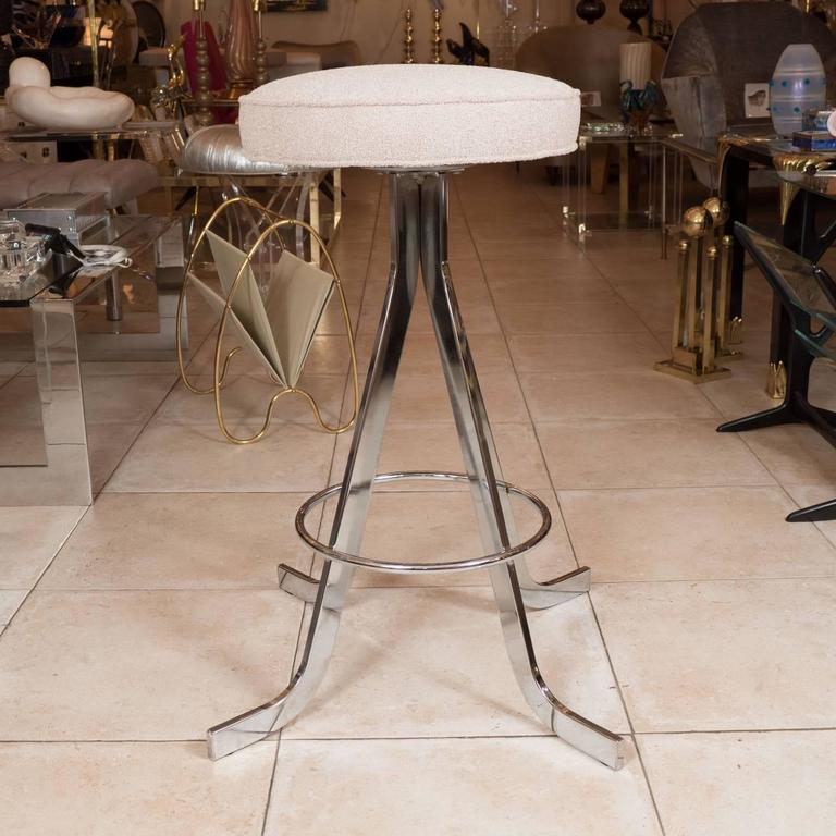 Set of four polished nickel stools with upholstered circular seats.