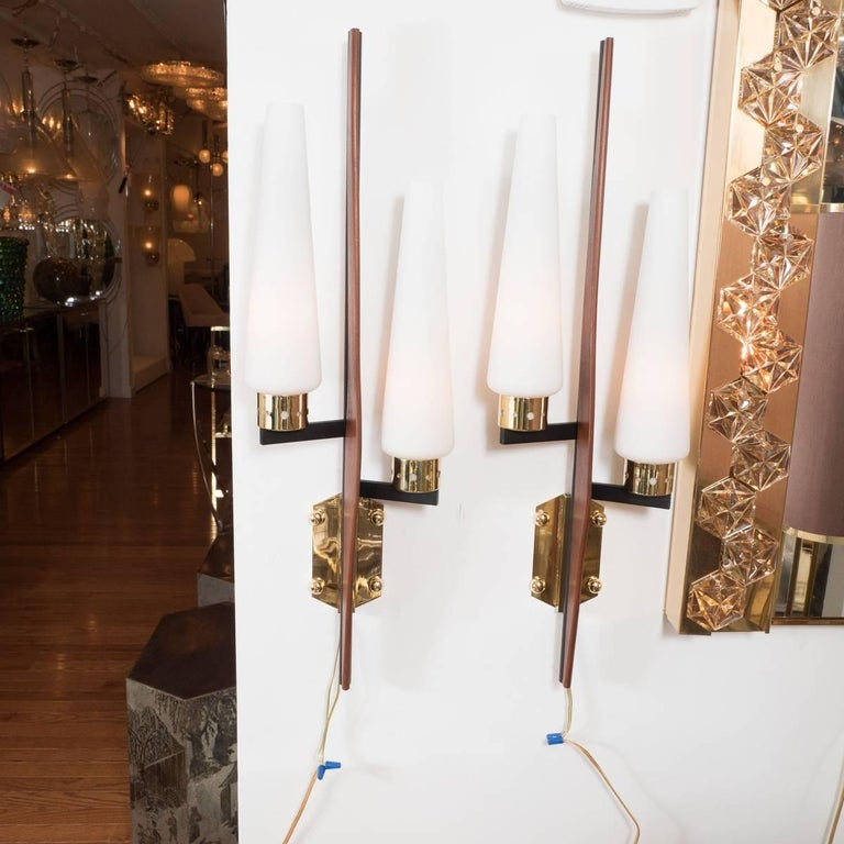 Two-arm, stylized brass, wood and enameled metal sconces with frosted glass shades.