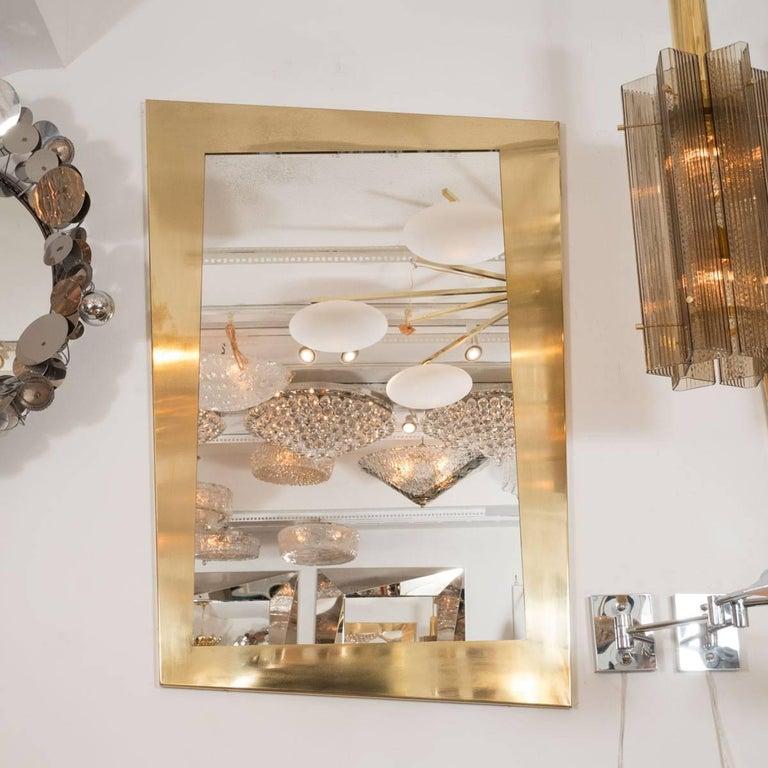 Polished brass trapezoidal mirror.