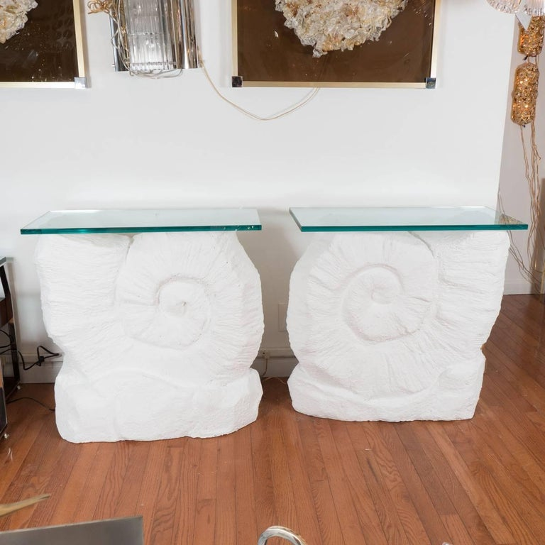 Pair of composition nautilus shell console tables with glass tops.