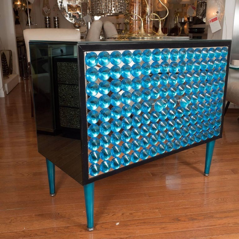 Lacquered wood and blue mirrored cabinet with applied glass element design on doors.