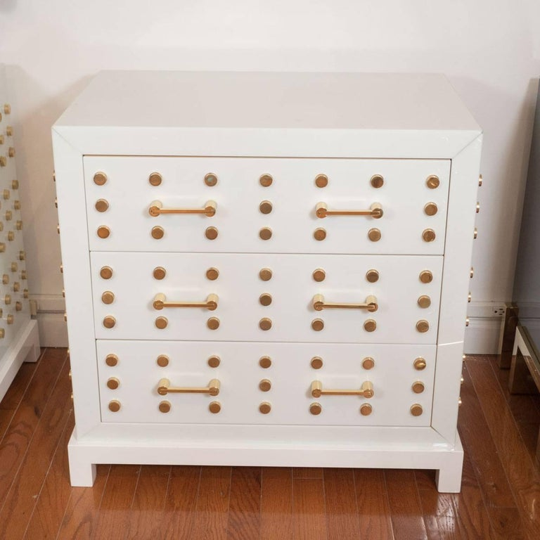 Pair of white, opaline glass chests of drawers with brass stud motif.