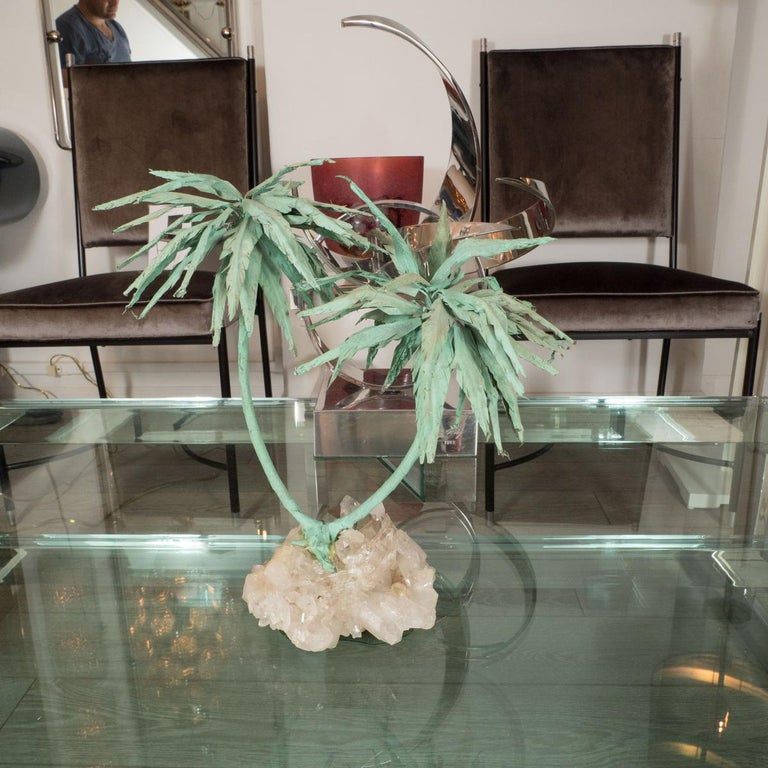Patinated palm tree form sculpture with quartz base.