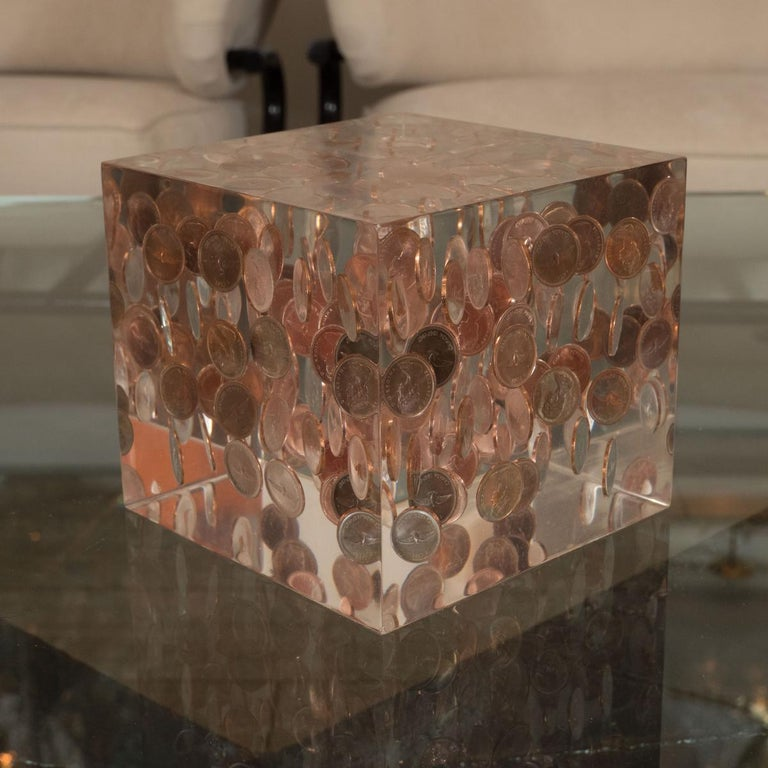 Cubic Lucite sculpture with encased coinage.