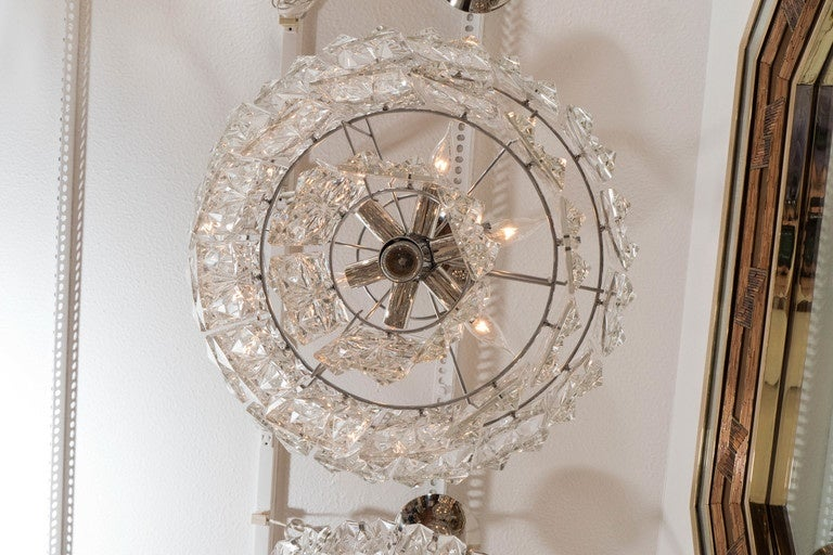 Three-tiered chandeliers composed of hexagonal, facet-cut crystal elements.