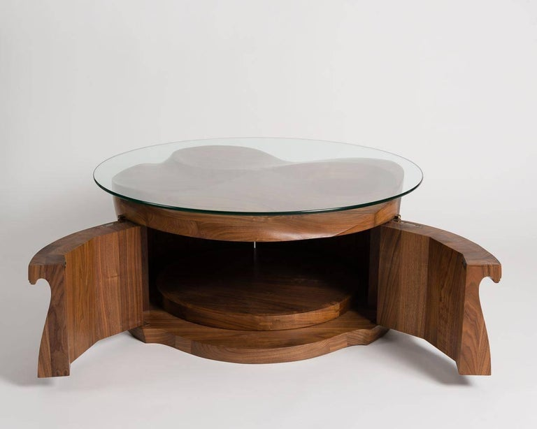 This sculptural table is carved into a flowing arrangement from solid, three and a half inch walnut, and features double doors that open up onto an interior cabinet with a revolving floor.