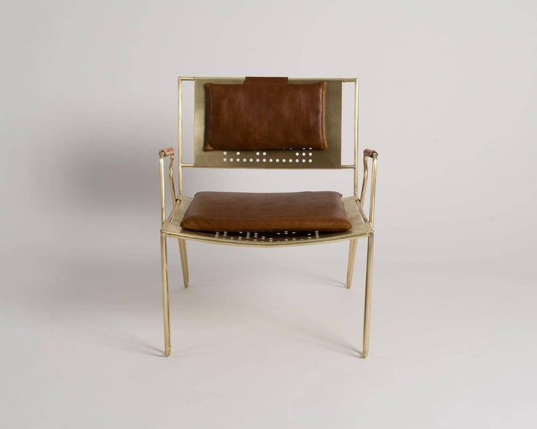 This dynamic, modern lounge chair, which can be used indoors or out, features removable leather pads, coiled copper armrests, and perforations in both the seat and back of its brushed bronze frame.