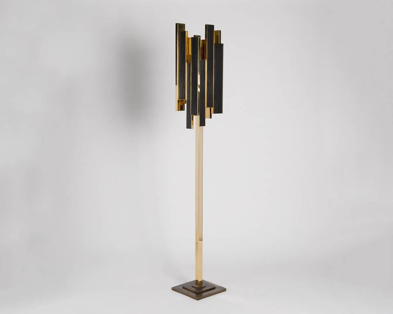 A floor lamp with a deco-inspired base and a shade composed of asymmetrical sections of burnt wood and polished bronze.