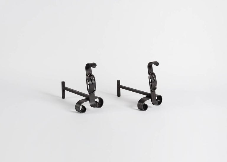 Pair of decorative andirons, each with a crowned with ornamental buckle.