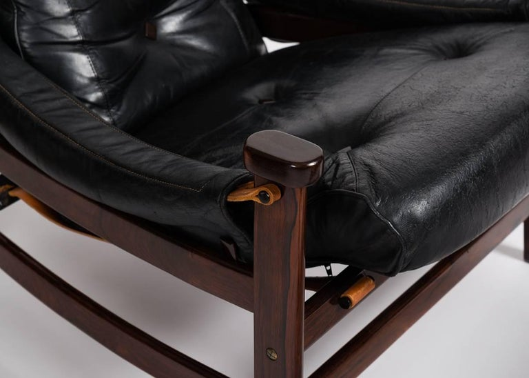 With its slung arms, reclined seat, and plush, leather upholstery, this chair, created by Jean Gillon in the 1960s, possesses a quintessential Brazilian aesthetic. The piece comes with its matching ottoman.  Possibly the bertioga design.