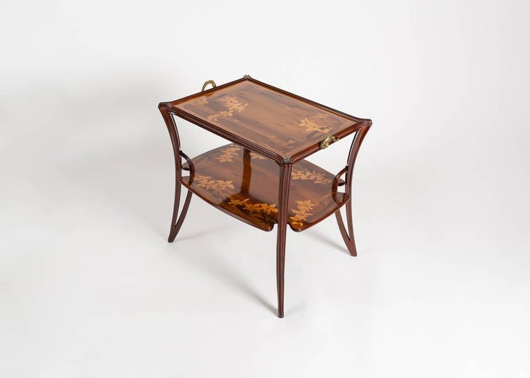 Both tiers of this remarkable fruitwood side table are decorated with an elaborate inlay depicting living matter, designed and executed by Louis Majorelle. The piece is supported by four elegantly bowed legs and accented with gilt bronze