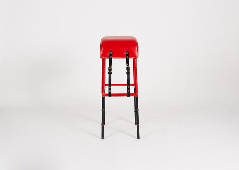 This spare bar stool in leather and painted cast iron sets up a stark contrast between form and composition. Constructed in sleek lines, and of Industrial and semi-Industrial materials, it nevertheless possesses an exuberant coloring and bold