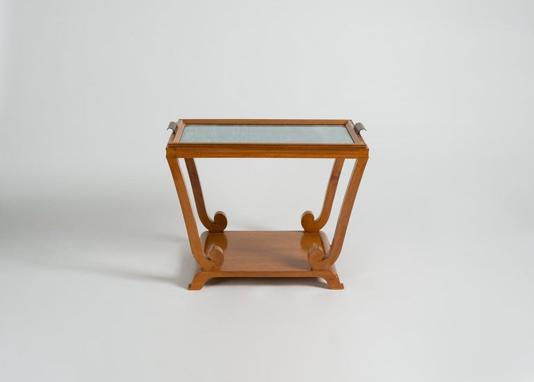 Remarkable Art Deco, two-tiered table with blue-backed, glass topped, removable top, brass handles, and swirled supports.