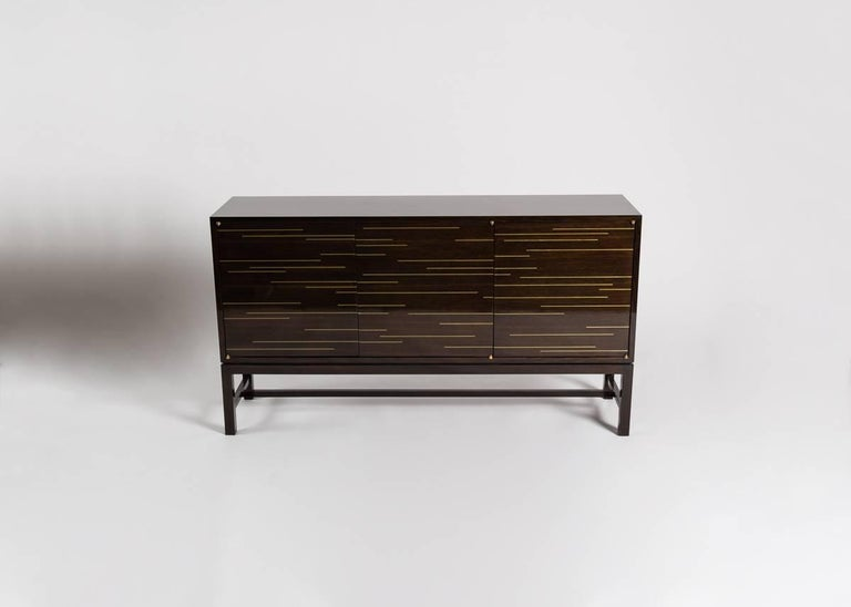 Zelouf & Bell are masters of creating refined, sophisticated custom pieces reflecting the unique needs and bespoke tastes of collectors and clients around the world.  This beautiful, dark, cabinet features brass details and four doors which open by