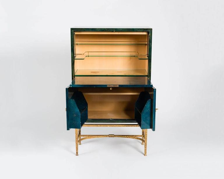 Lacquered wood and gilt bronze bar cabinet, in the manner of Jacques Adnet and Gilbert Poillerat.