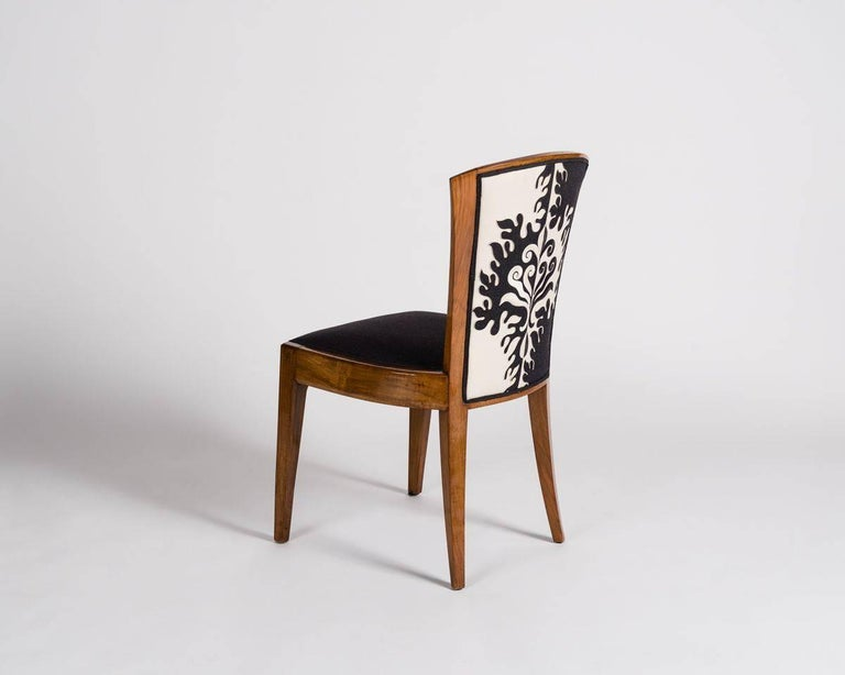 This model was executed by Dominique with different variations as early as 1924. Each chair in this freshly reupholstered set flares at its top, balancing a wide seat.