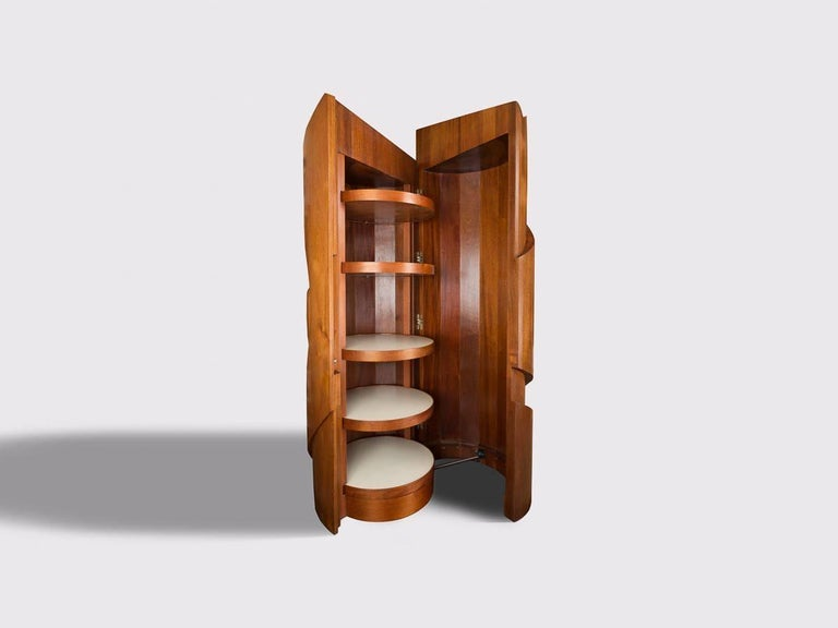 This sculptural cabinet is carved from solid, 4-inch thick Mahogany, and weighs 900 lbs. It is divided in two halves. One half is a door, which swings out on hidden hinges and concealed casters. The other half contains revolving shelves and drawers.