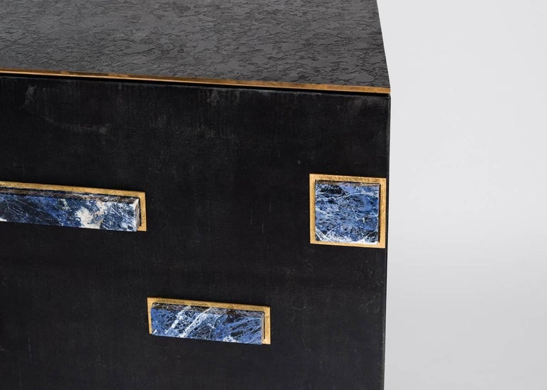 A two-door bar cabinet clad in parchment, topped in bronze, and featuring a series of ornamental onyx rectangles on its face, by Rome based architect Achille Salvagni, recognized worldwide for bringing together Italian craftsmanship and his passion