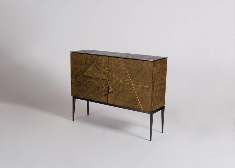 Giò is a double-door cabinet of lacewood with a burnished cast bronze top, 24-karat gold-plated and polished accents, inset cast-bronze handles, and polished brass inset details. An homage to the Italian designer's predecessor Gio Ponti, the cabinet