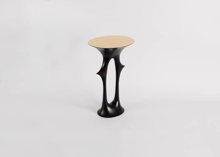 A side table with a solid, patinated bronze base, a polished bronze top and, despite its thorn motif (familiar to the work of van der Straeten) a shape reminiscent of the human form.
