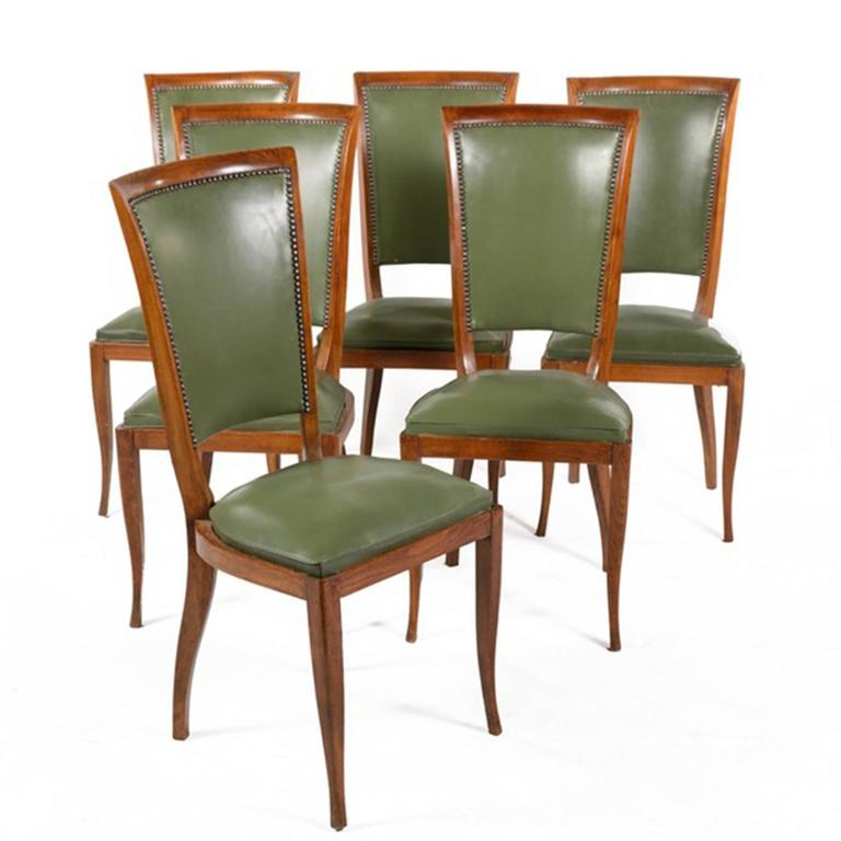 A group of six vintage upholstered dining side chairs. The wooden frames are upholstered in green vinyl with brass tone tacks lining the backs. They feature slightly curved crests above padded backs and cushioned seats. The chairs rise on gently