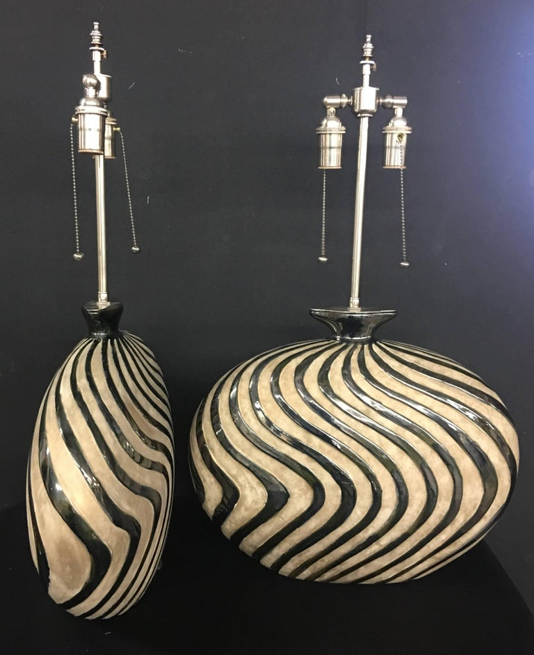 Unusual pair of whimsical ceramic vessels with lamp application. The vessels are in a mottled cream background with raised silver glazed waves. The hardware is polished nickel. The vessels are 15.5