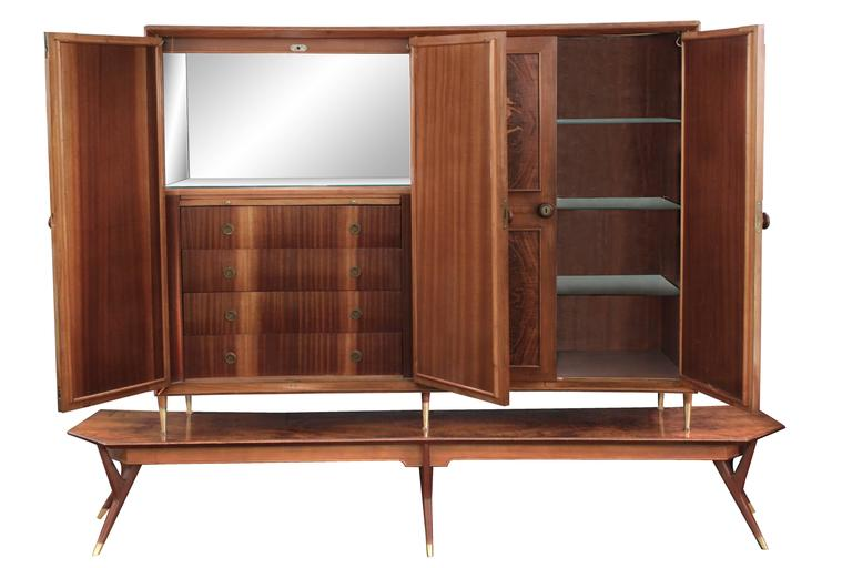 Four-door cabinet with exquisite figural inlays in exotic woods on sculptural base by Eugenio Diez, Buenos Aires, Argentina, 1940s. Each door has two raised and illuminated panels with inlays. The left side interior is an illuminated cabinet with