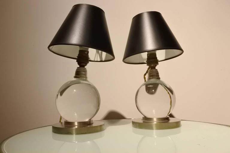 Rare pair of Adnet lamps made with Baccarat crystal and a nickel base. The balls can be moved to different positions. These lamps are from the 1940s and are documented in the Adnet book (model 7706).
