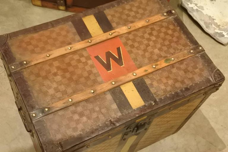 Rare Louis Vuitton Damier trunk with original monogram and striping. Perfect size for a side or end table. These trunks bear the character and craftsmanship of traveling with style in the old-world.