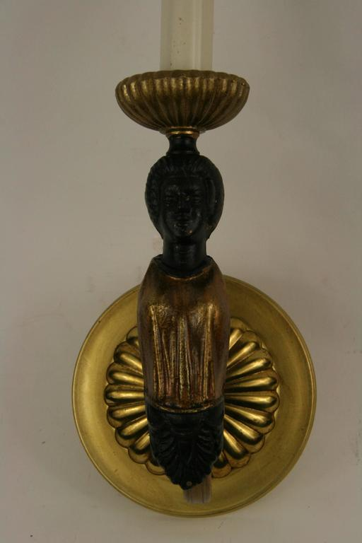 #2-3029, a pair of figural single arm sconce in a black and brass finish. NO ADDITIONAL DISCOUNTS ON SALE ITEM