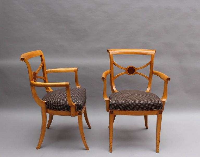 A set of 12 French Art Deco side and 2 arm sycamore dining chairs by Ernest Boiceau in the Neoclassical style. Documented page 36 and 37 of the catalog by Galerie Willy Huybretchs (Expert S.F.E.P)  Dimensions arm chairs  H 32