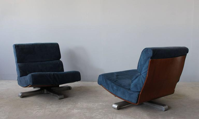 Four French 1970s bent molded rosewood frame lounge chairs on a cast aluminum swivel base.