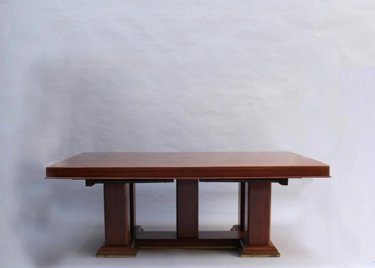 Mounted on a five-pedestal mahogany base with bronze details, the table can receive four end leaves for a total length of 13'2