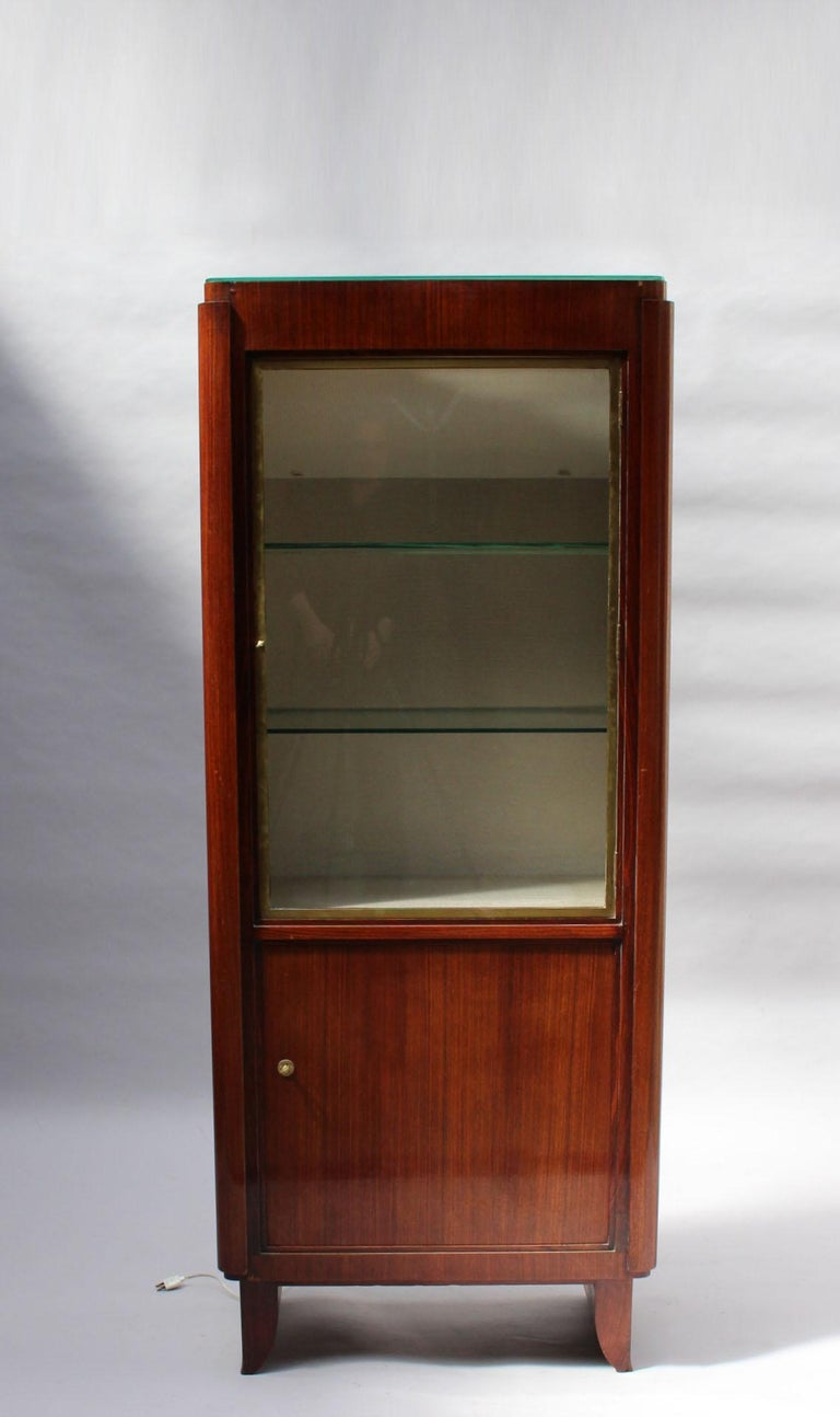 A fine French 1030s rosewood vitrine by Maxime Old with a plain lower door and a bronze framed upper glass door opening on an upholstered interior with glass shelves. Inside lighting for the shelves plus another lighting coming from inside the glass