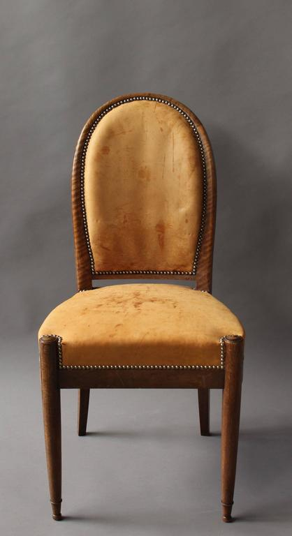 A set of six fine French Art Deco walnut dining / side chairs with an oval shape back and some exquisite carved wooden details, circa 1925.